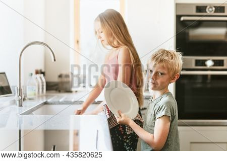Young boy wiping dishes in kitchen, basic house chores
