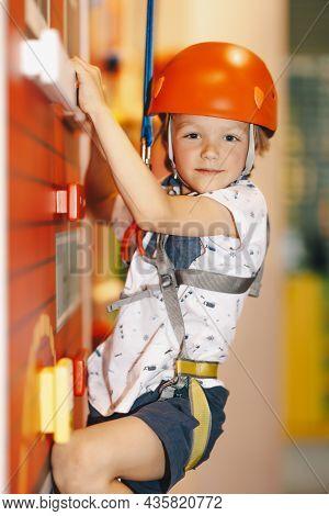 Indoor Climbing Class For Kids. Little Boy In Red Helmet Climbing The Wall In Bouldering Center. Sch