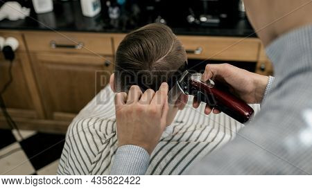 Man Getting Haircut By Barber While Sitting In Chair At Barbershop. Barbershop Theme