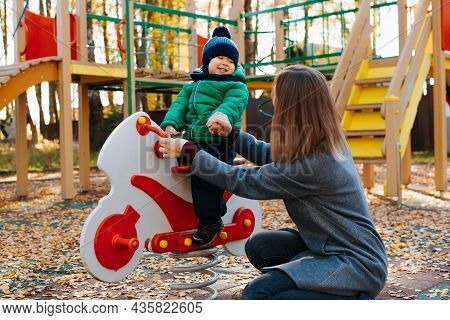 Young Mother With Child Playing On Playground, Mom Holding Hand Of Laughing Cheerful Baby Kid Swingi