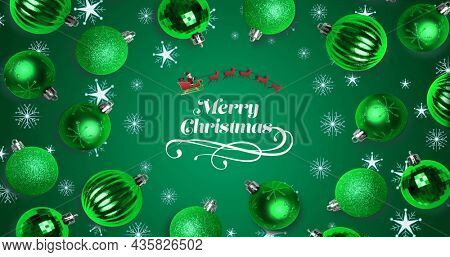 Image of snowflakes and baubles over merry christmas text on green background. christmas, tradition and celebration concept digitally generated image.