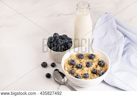 Oatmeal With Blueberries And Milk On A Light Background. Breakfast Top View With Copy Space.