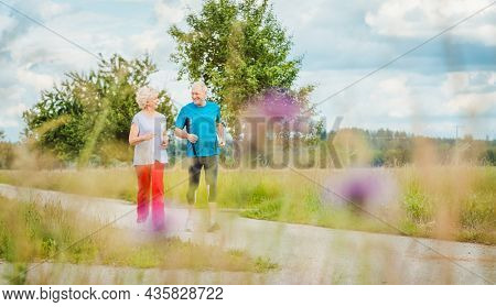 Fit and active senior couple running outdoors as exercise