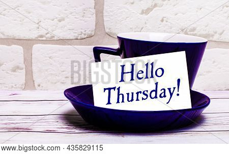 On A Light Background, A Blue Cup With A Saucer And The Inscription Hello Thursday