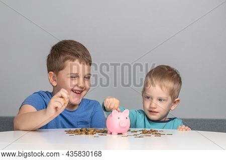 Two Children Laugh And Put Coins In Piggy Bank. Boys Smile And Invest