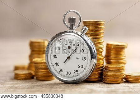 Time Is Money. Fast Profits. Stopwatch And Stacks Of Coins In The Background
