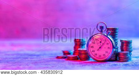 Fast Money Or Money Is Time. Stopwatch And Stacks Of Money Coins In Neon Light. Template Copy Space