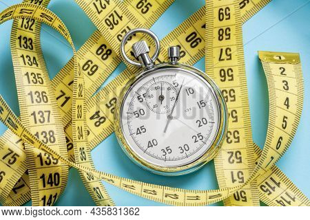Weight Loss Workouts. Yellow Measuring Tape Meter And Stopwatch On A Blue Background