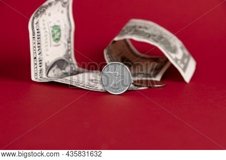 Uae Currency Dirham Coin, Set Against Paper American Dollars And Red Background. Copy Space.