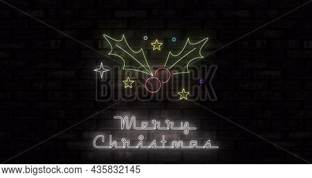 Image of neon merry christmas text and holy on black background. christmas, winter, tradition and celebration concept digitally generated image.