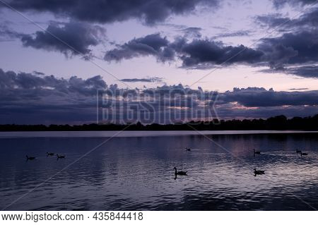 Magnificent Sunset Skies With Dark Menacing Clouds Above The Lake Reflecting Sky With Clouds And Duc