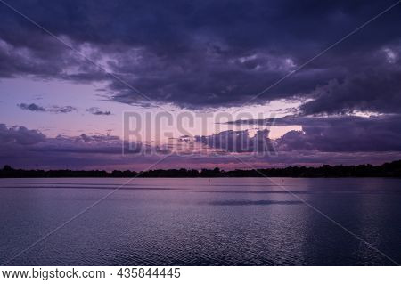 Magnificent Pink Sunset Skies With Dark Menacing Clouds Above The Lake With Sky With Clouds And Refl