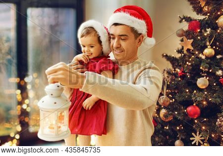 winter holidays and family concept - happy middle-aged father with baby daughter in in santa hat holding lantern at window over christmas tree at home