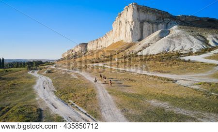 A Group Of Riders On Horseback Moves Along The Canyon Along The White Rocky Mountain. Shooting From