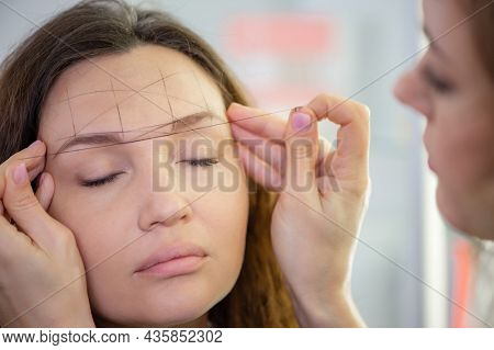 Makeup artist draws the shape of a woman's eyebrows in a beauty salon. Cosmetologist forms the eyebrow line with a black thread on a female face.