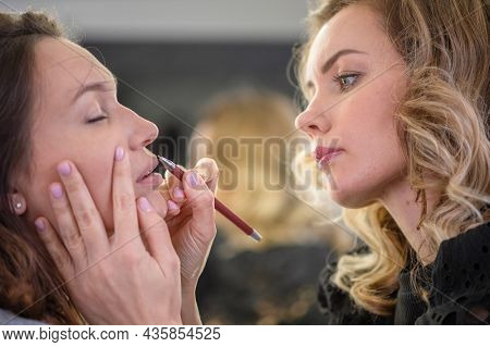 Young woman making makeup in a dressing makeup room. Lips make up process. Make-up artist in beauty studio doing makeup for beautiful girl. Profile - woman making up using pencil for lips. Making mua.