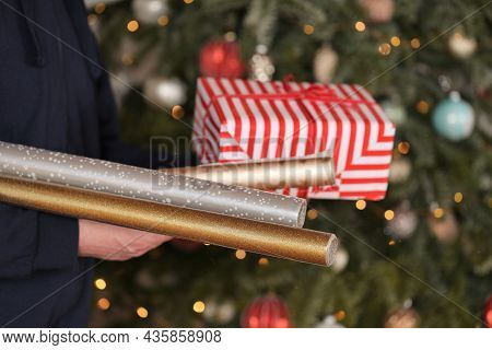Gift Paper. Rolls Of Christmas Gift Paper In Hands On Christmas Tree Background. Packaging For Chris