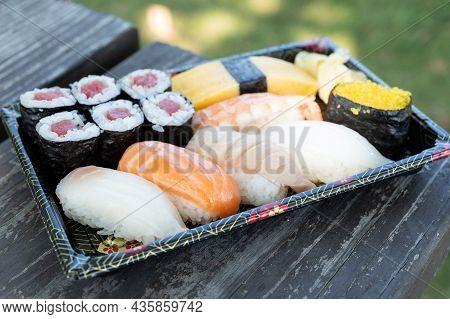 Japanese Food Sushi, Sashimi, Nigiri And Tuna Roll Set On Picnic Table Outdoor