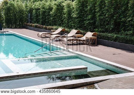 Swimming Pool Ladder And Sun Lounger In Poolside, Luxury Outdoor Swim Pool And Modern Decoration Of