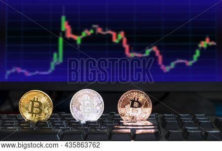 3 Different Colored Bitcoin Digital Currency On Computer Keyboard With Blurred Background Of Investi