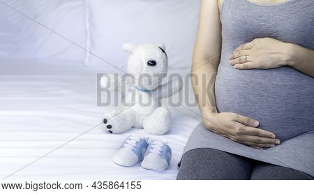 Image Of A Woman Pregnant In Gray Maternity Dress With Baby Shoes, Doll Sitting On Bed. Mom Is Touch