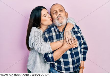 Young brunette woman and senior man standing over pink background. Daughter and father hugging and bonding together as happy family