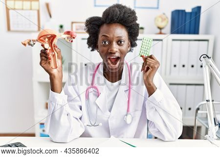 African doctor woman holding anatomical female genital organ and birth control pills afraid and shocked with surprise and amazed expression, fear and excited face.