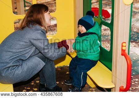 Happy Family On Playground, Mom And Baby Play In Children's Toy House Outdoors. Laughing Young Mothe