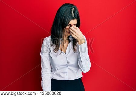 Young hispanic woman wearing business shirt and glasses tired rubbing nose and eyes feeling fatigue and headache. stress and frustration concept.