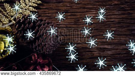 Image of snow falling over pine cone at christmas. christmas, winter, tradition and celebration concept digitally generated image.