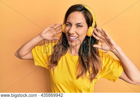 Young latin woman listening to music using headphones winking looking at the camera with sexy expression, cheerful and happy face.