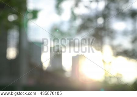 Blur City And Trees With Lens Flare During Sunset. Business Or Urban Background Concept.