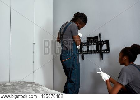 Teamwork Of Young Handyman And Female Apprentice. Tv Hanger Bracket Installation On Grey Wall In Liv