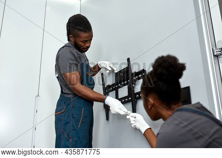 Low Angle Skilled Mixed-race Mount Service Worker In Gloves Taking Tool From Female Apprentice, Sitt