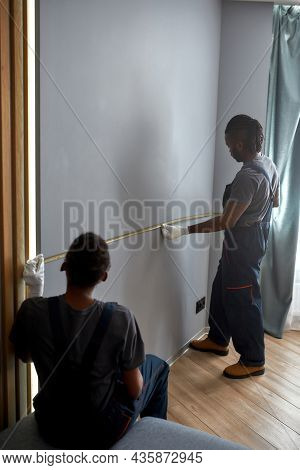Mixed-race Man And Woman In Workwear Holding Measure Tape, Measuring Wall To Install Large Flat Scre