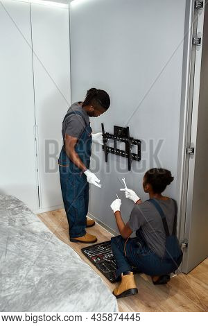 Back View Mixed-race Handyman In Overalls Mounting Black Tv Hanger On Grey Wall In Living Room. Fema