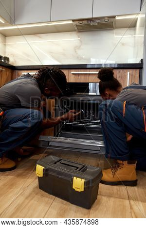 Back View Professional African American Repairman Together With Young Female Apprentcie Looking Insi