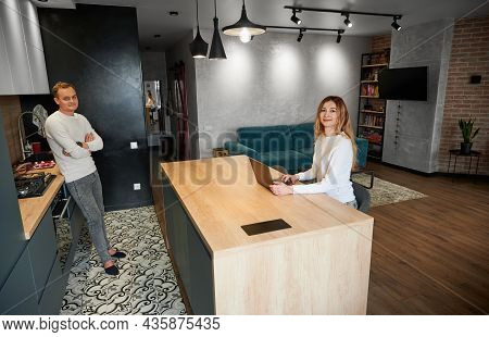 Young Woman And Man Working Or Studying On Laptop With Good Mood In Modern Kitchen At Home. Concept