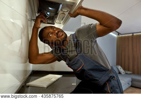 Closeup Portrait African American Professional Electrician Repairing Under Cabinet Range Hood And Ch