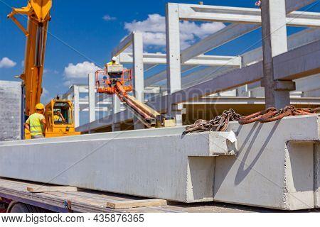 Trailer Truck Is At Unloading Cargo, Concrete Beam For Assembling Concrete Edifice, Building Site. C