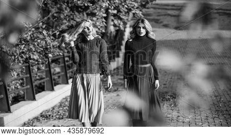 Friends Girls. Fall Fashion. Pleated Skirt Fashion Trend. Women Walking In Autumn Park. Autumn Styli