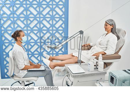 Positive Delighted Visitor Looking At Her Nail Master