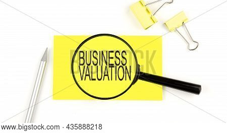 Business Valuation Text On The Sticker Through Magnifier. View From Above. Business