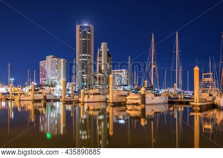 Corpus Christi, Texas, USA downtown skyline on the water at twilight with boats.