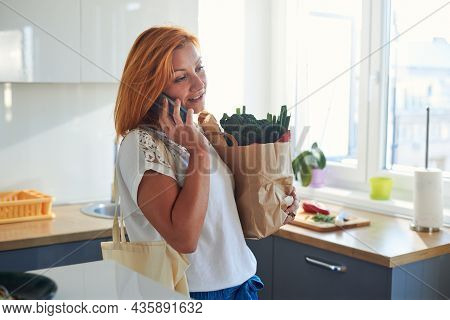 Woman cooking food while speaking on cellphone.woman cooking food in kitchen using cellphone. Cooking food lifestyle. Cooking food. woman cooking food at home while speaking on cellphone. Lifestyles. Healthy food cellphone Food cooking woman lifestyle Foo