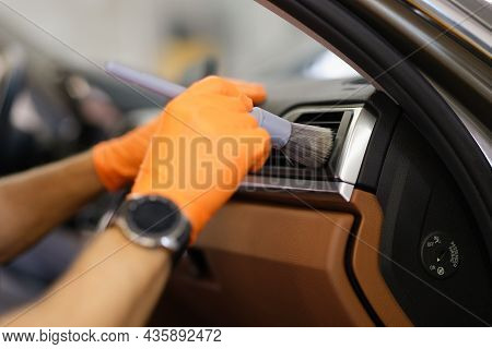 Master Mechanic In Rubber Gloves Wiping Air Conditioner Of Car With Brush Closeup
