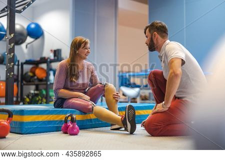 Woman with prosthetic legs talking to a trainer while doing physiotherapy