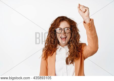Encouraged Redhead Woman Cheering, Raising Fist Up And Shouting, Chanting Or Rooting For Someone, Pr
