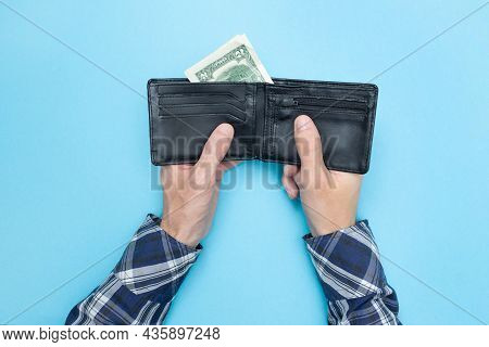 Young Man Holds A Wallet In Which There Are Only Two Dollars. Blue Background. Bankrupt. Money Is Ti