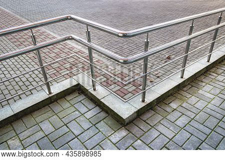 A Ramp And Metal Railings At The Entrance To The Residential Building For The Convenience Of People